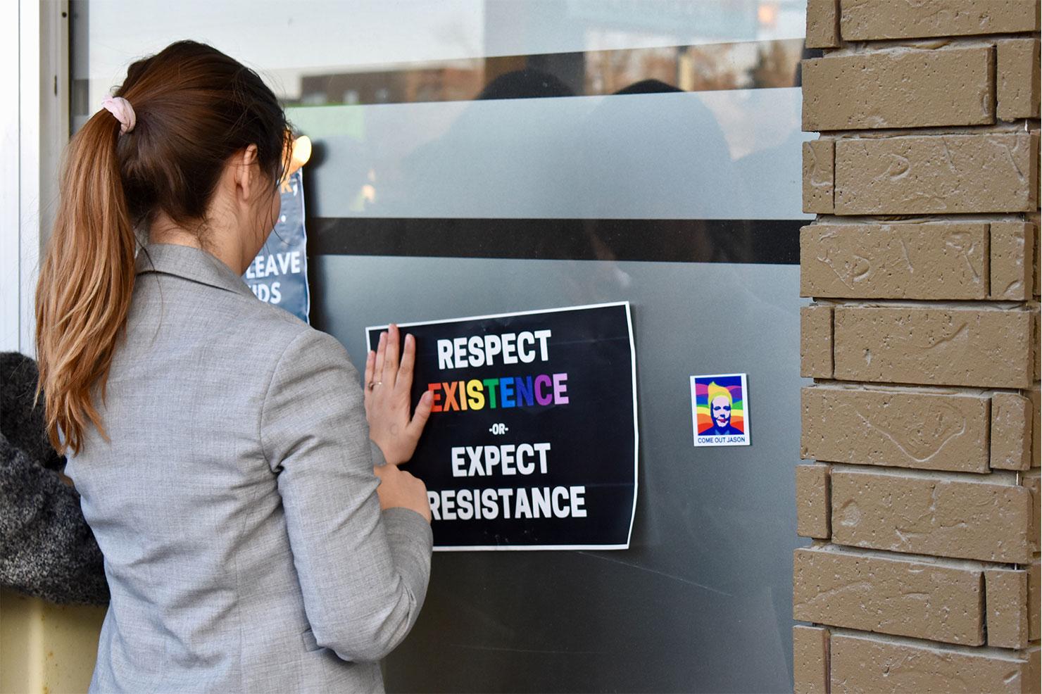 """Eine Person die an einem Fenster ein Plakat mit der Aufschrift """"Respect existence or expect resistance"""" anbringt."""