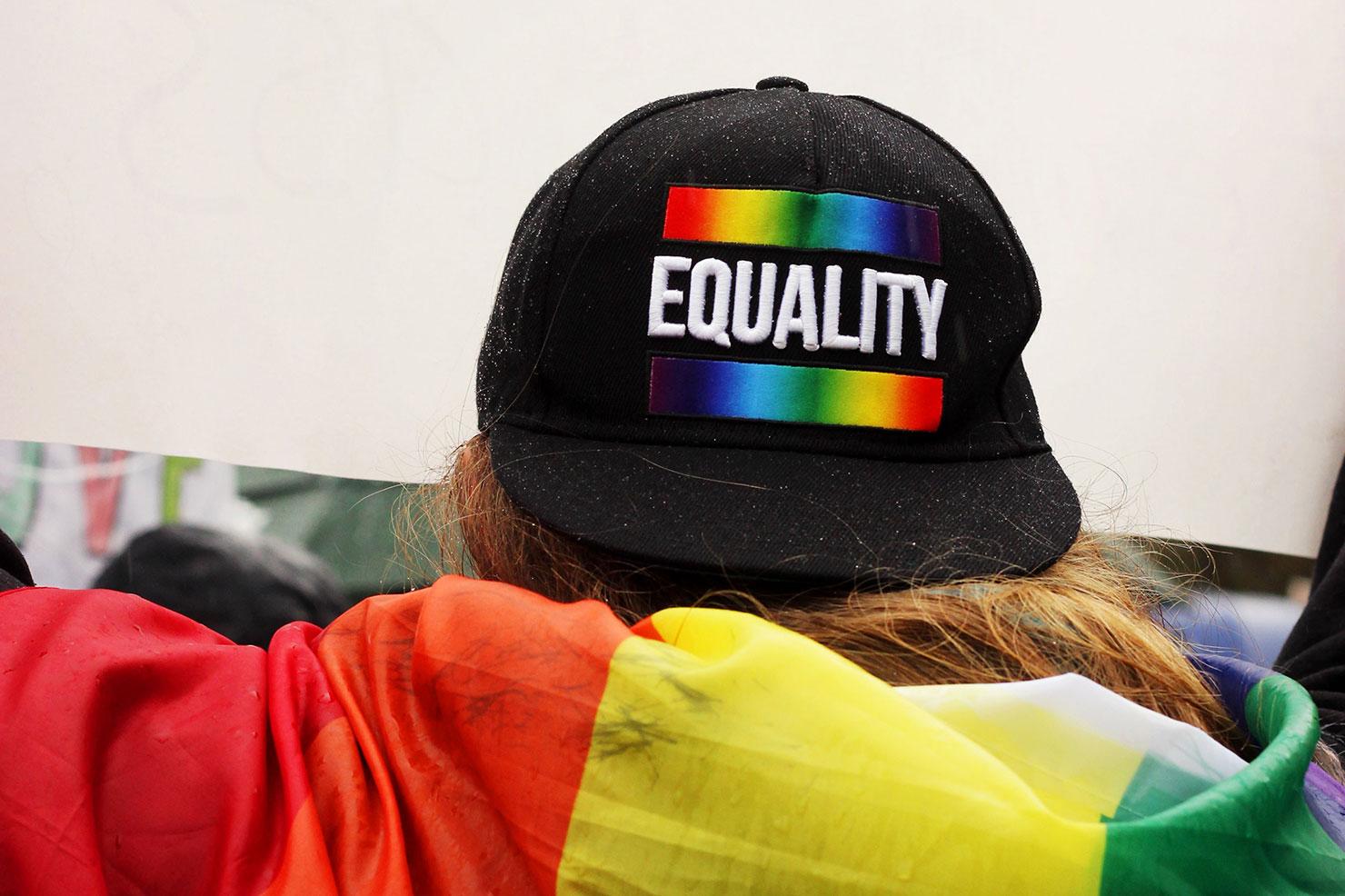 """Eine Person hat eine Regenbogenfahne umgehängt und steht mit dem Rücken zur Kamera. Sie trägt eine schwarze Kappe auf der in regenbogenfarben steht """"Equality""""."""